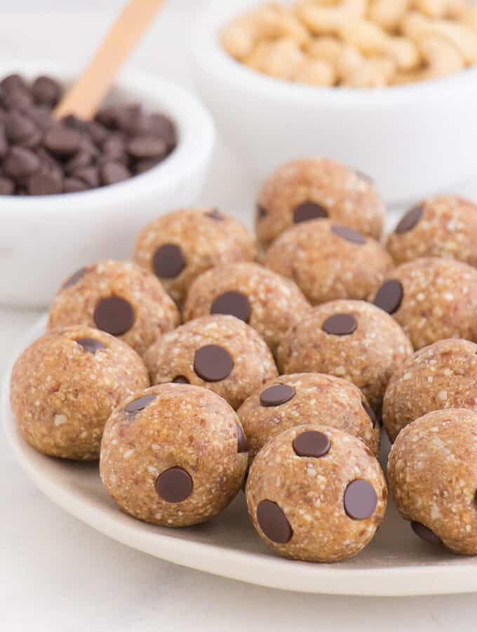 chocolate chip cookie dough balls sitting on a white plate