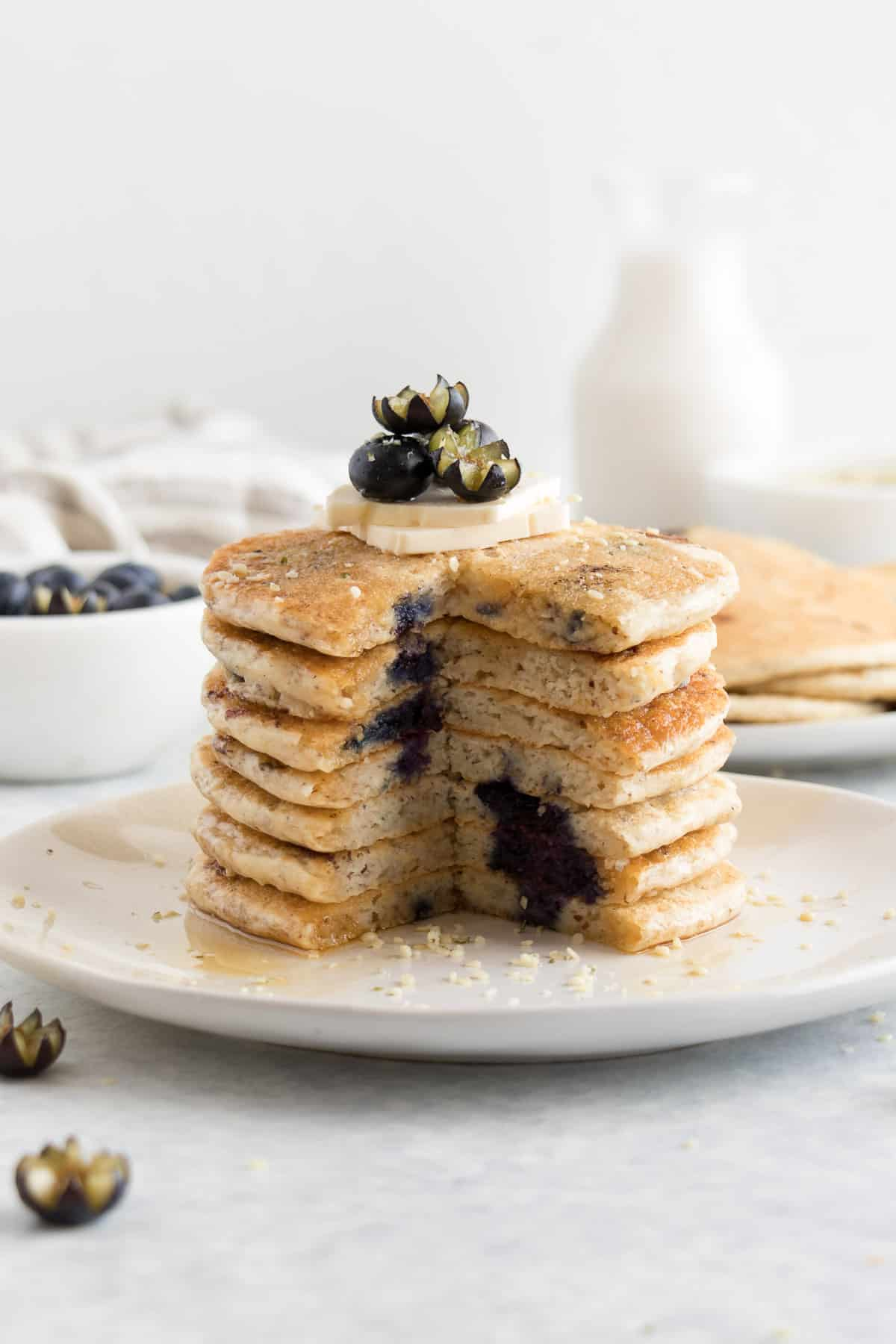 a sliced stack of fluffy pancakes with blueberries and butter