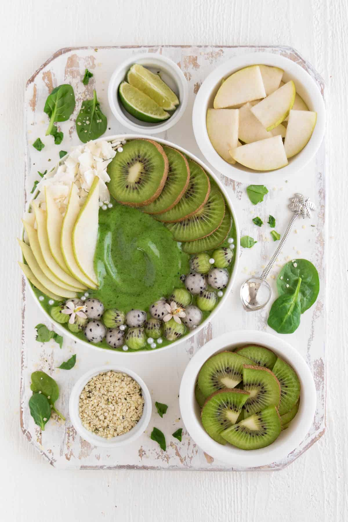 a white distressed cutting board with small bowls of hemp seeds, lime, kiwi, and pear