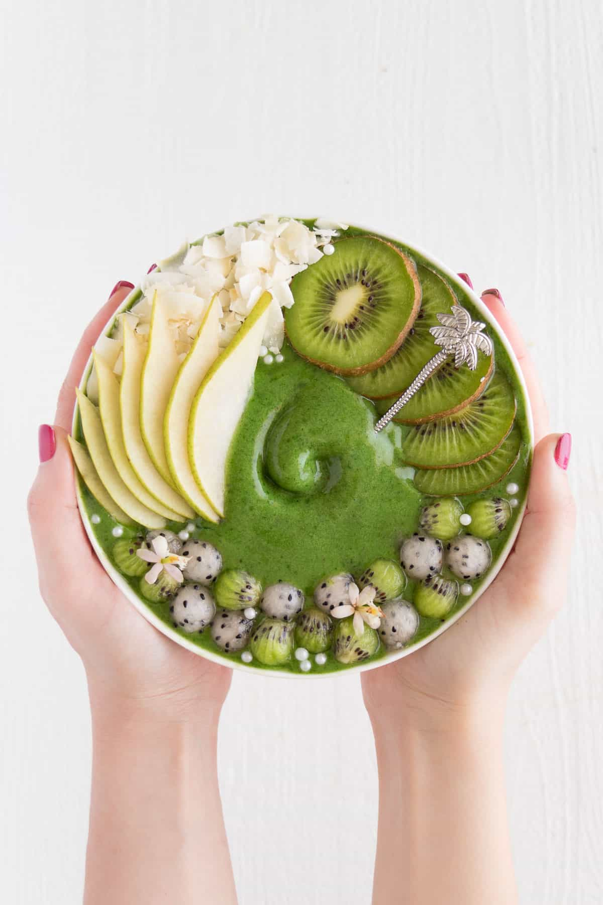 two hands holding a kiwi and pear smoothie bowl