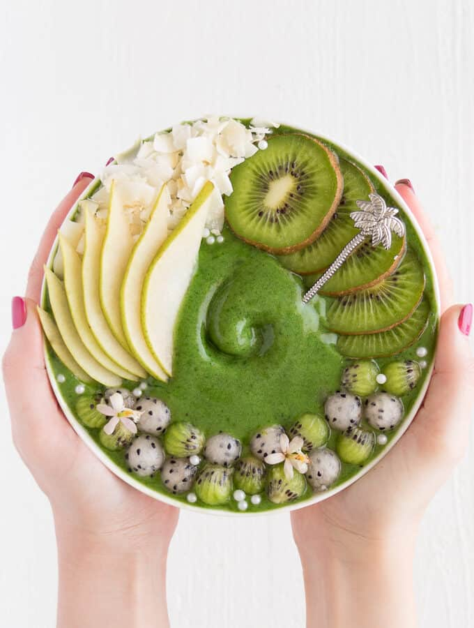 two hands holding a green smoothie bowl