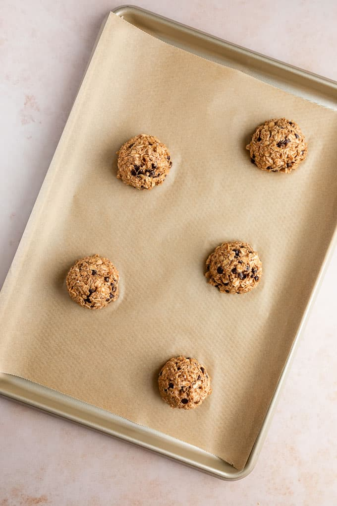 five balls of peanut butter banana oatmeal cookie dough on a baking sheet