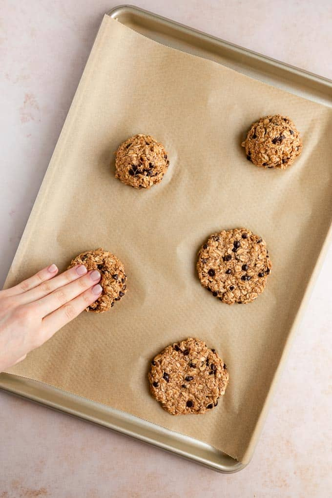 a hand pressing balls of chocolate chip banana oatmeal cookie dough on a baking sheet