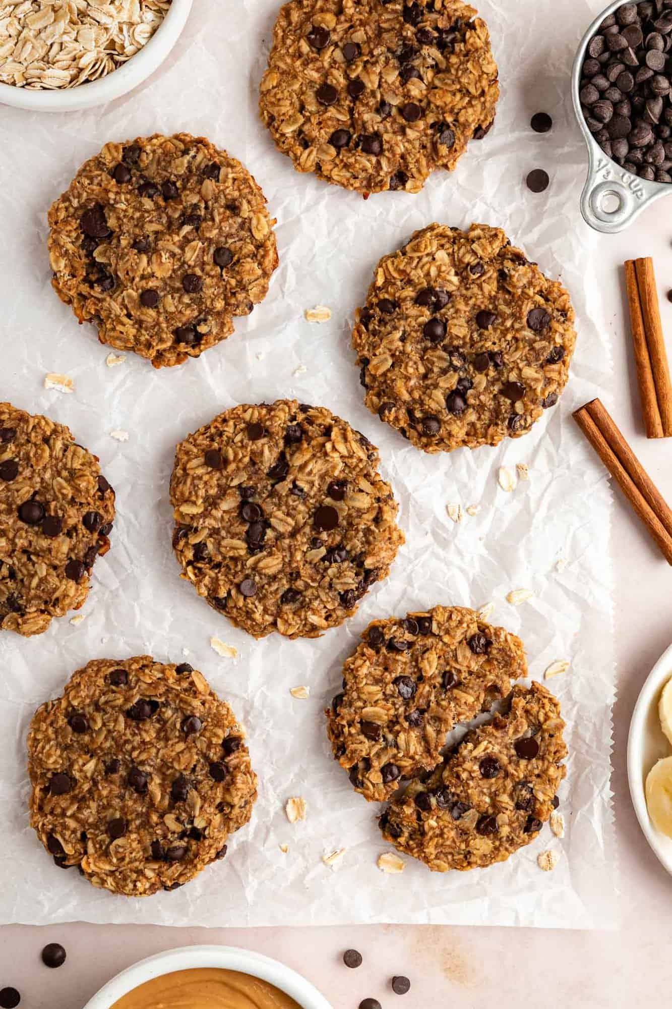 peanut butter chocolate chip banana oatmeal cookies laying on white parchment paper surrounded by ingredients in white bowls