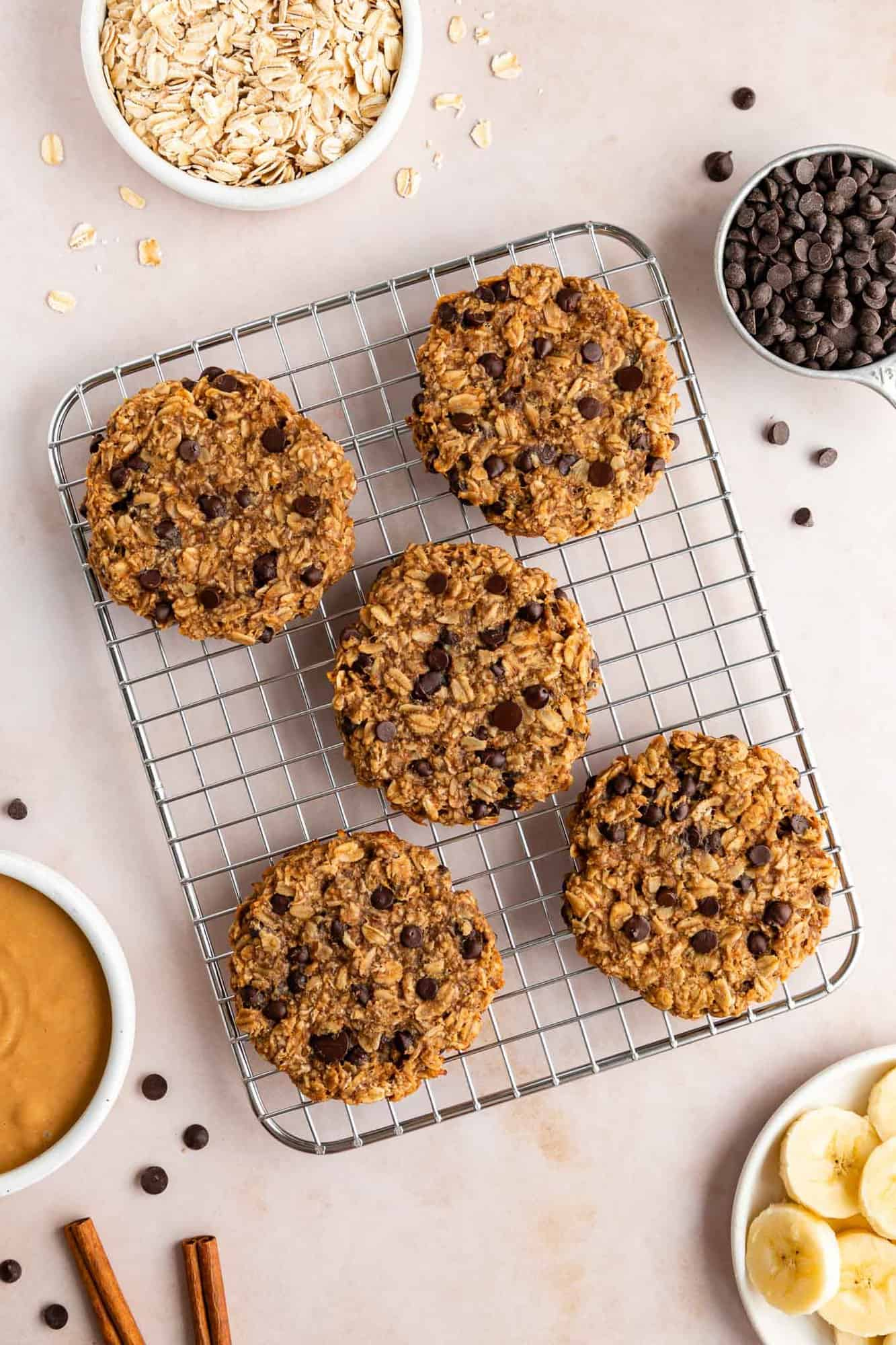 five peanut butter banana oatmeal cookies on a wire cooling rack surrounded by bowls of ingredients