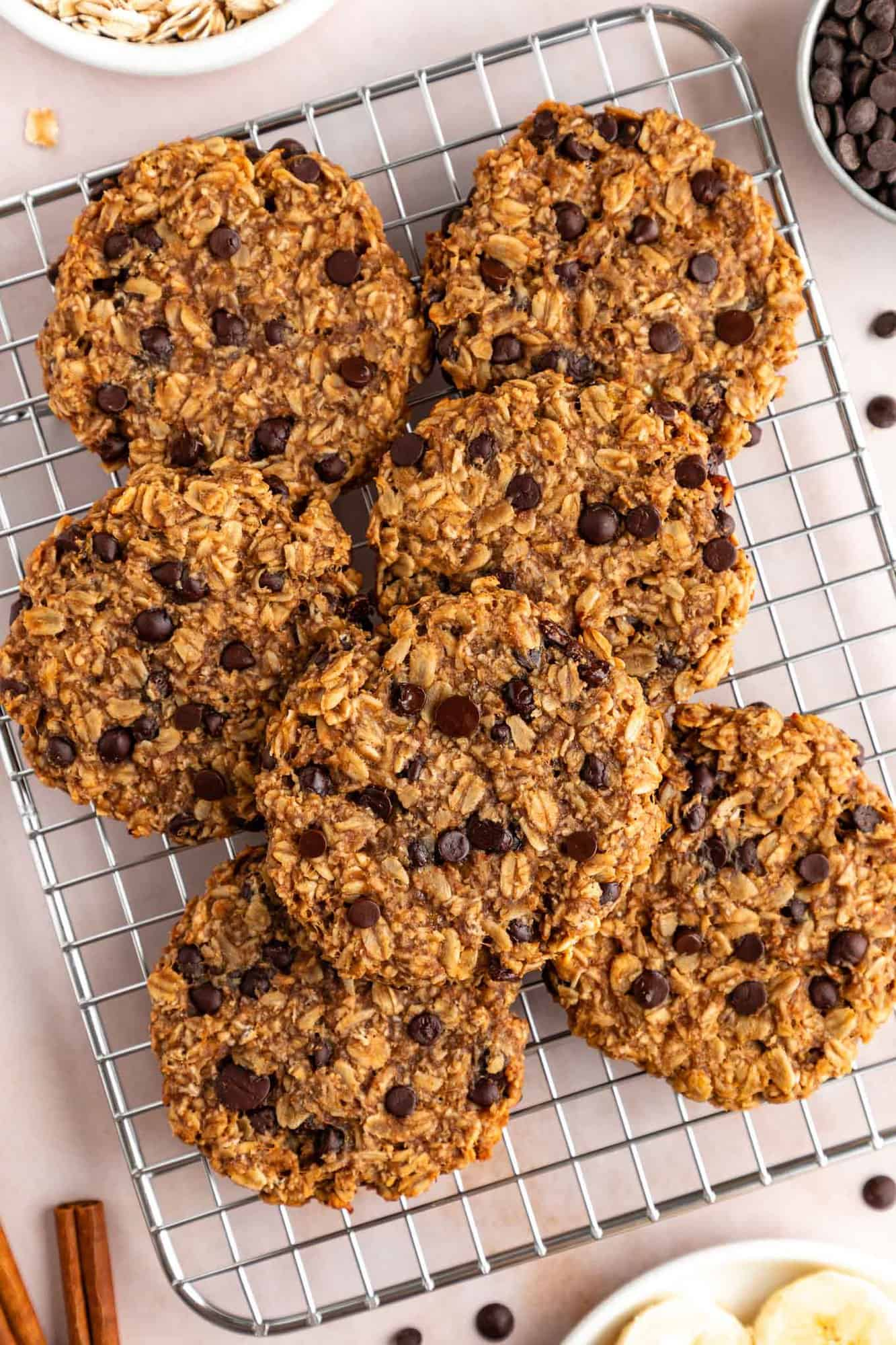 a pile of chocolate chip peanut butter banana oatmeal cookies on a wire cooling rack