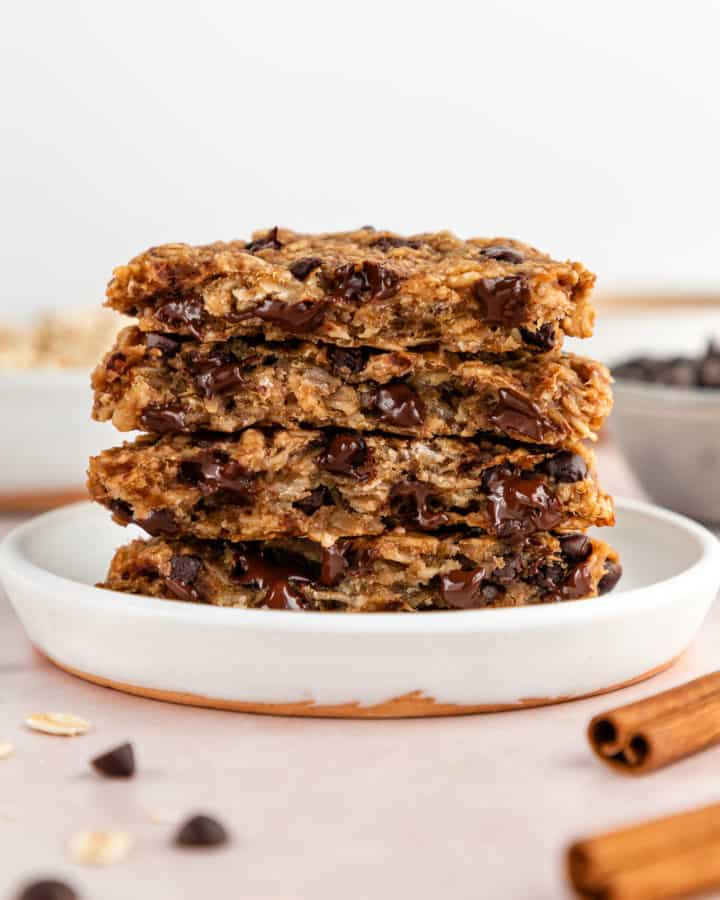 a stack of peanut butter banana oatmeal cookies with chocolate chips on a small white plate