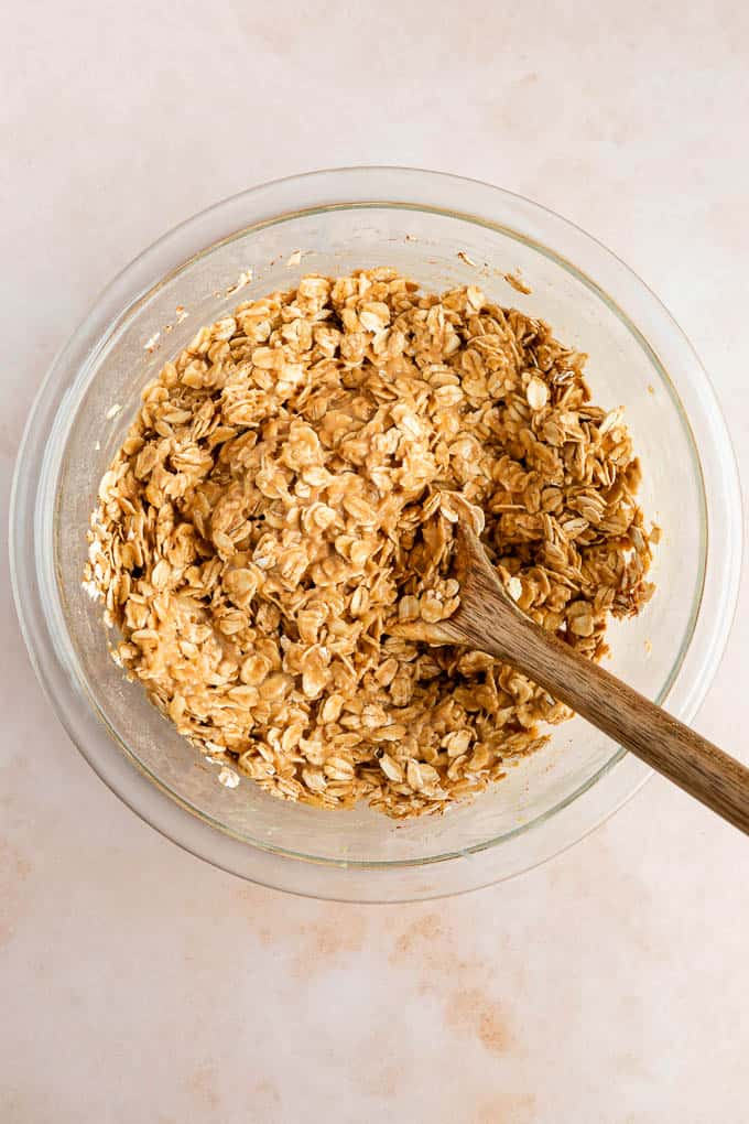 a wooden spoon mixing peanut butter banana oatmeal cookie dough in a glass bowl