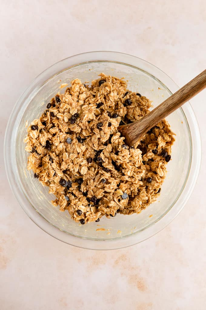 chocolate chip peanut butter banana oatmeal cookie dough in a glass bowl with a wood spoon