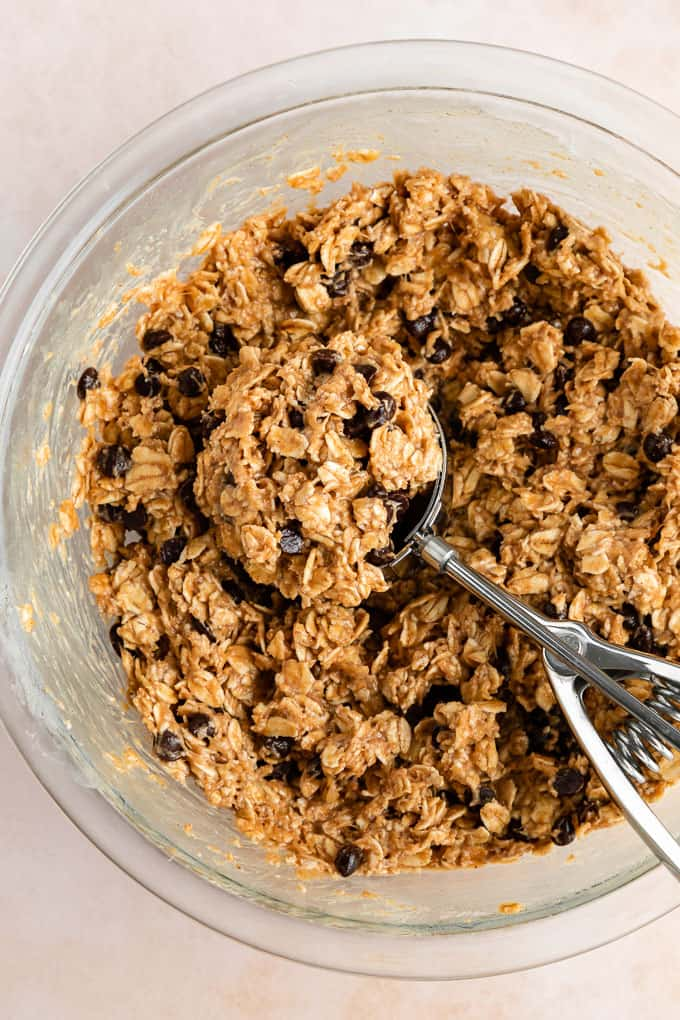 a cookie scoop scooping peanut butter banana oatmeal cookie dough in a glass bowl