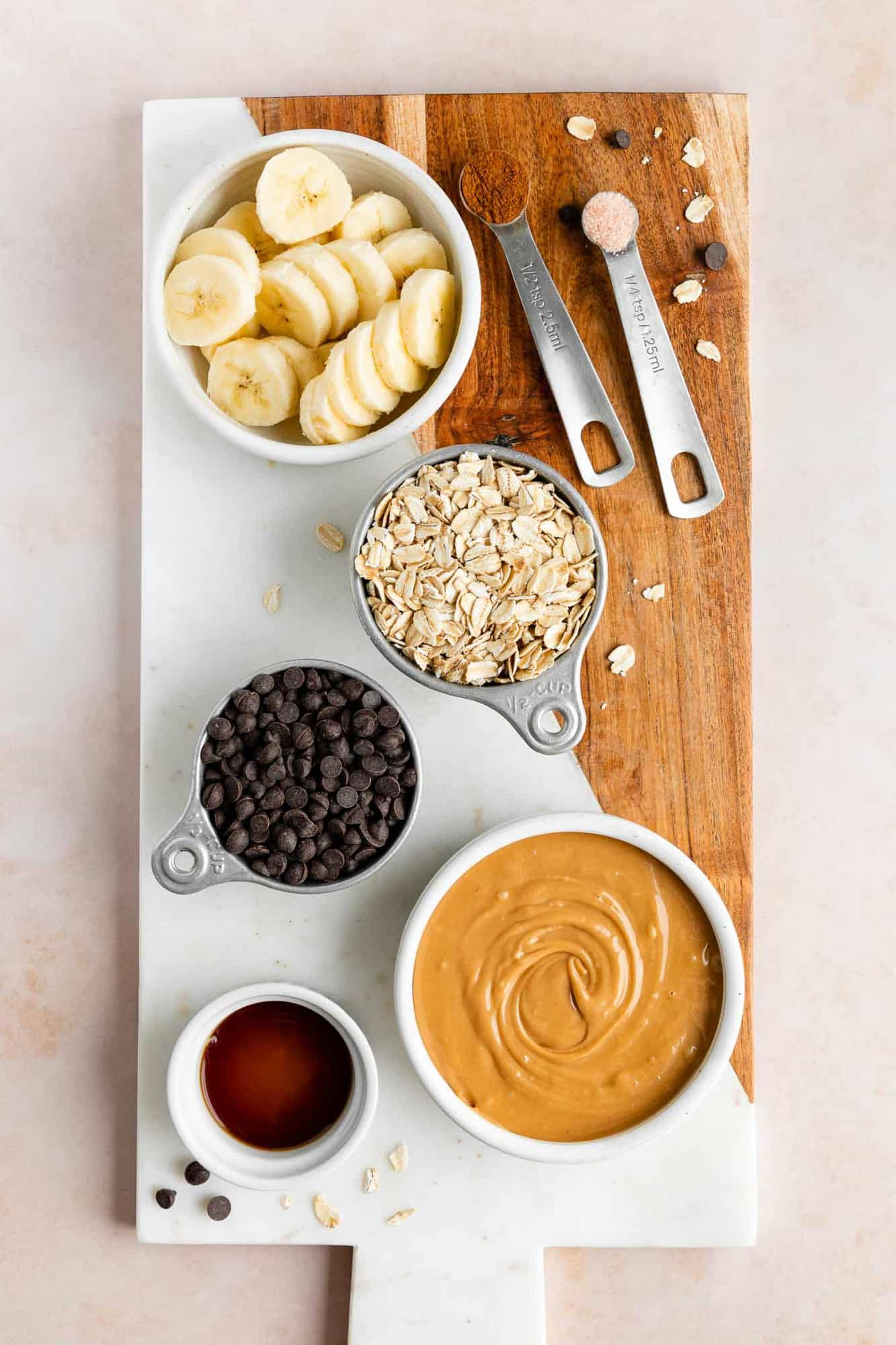 a wood and marble cutting board topped with bowls of ingredients, including sliced banana, peanut butter, chocolate chips, rolled oats, cinnamon, and vanilla extract
