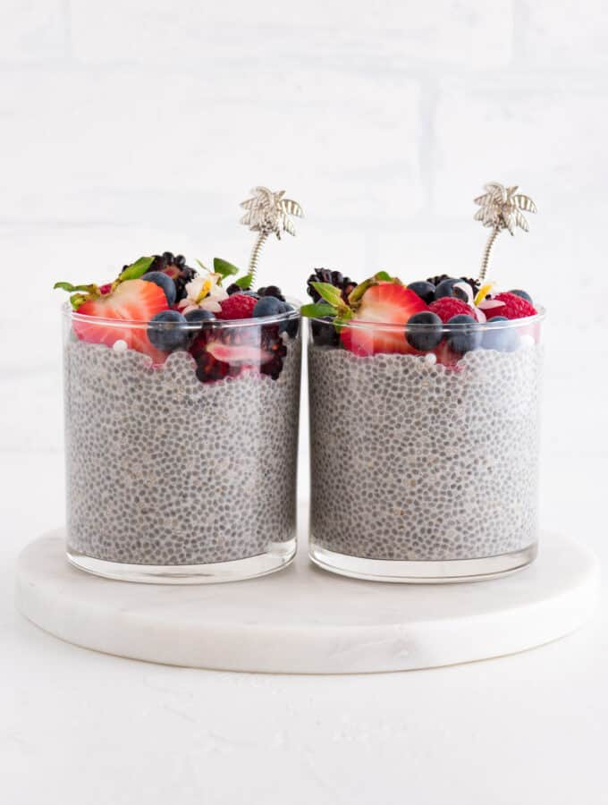 two glasses of vanilla chia pudding with fruit on top