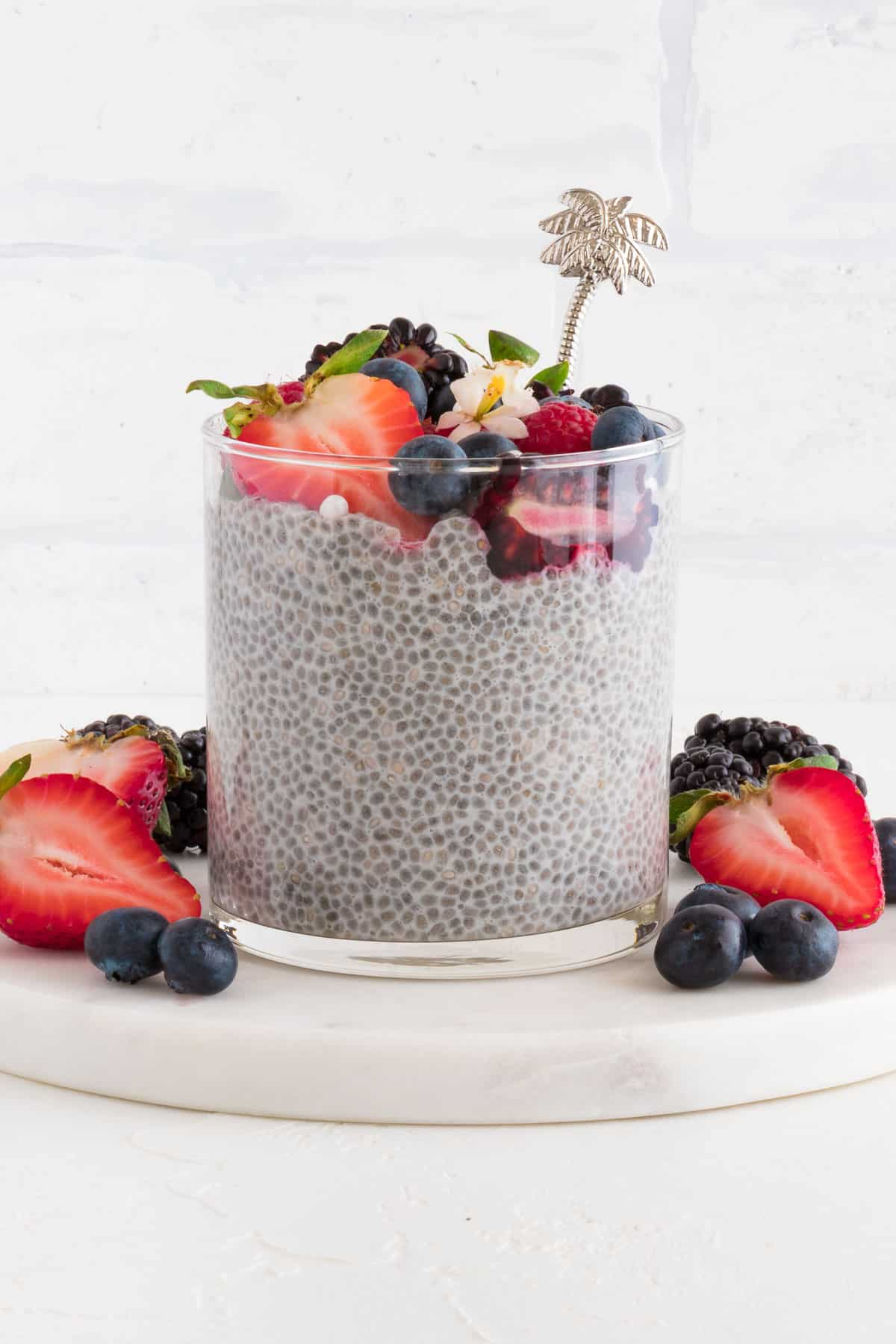 a glass containing chia pudding with strawberries, blueberries, blackberries, and raspberries