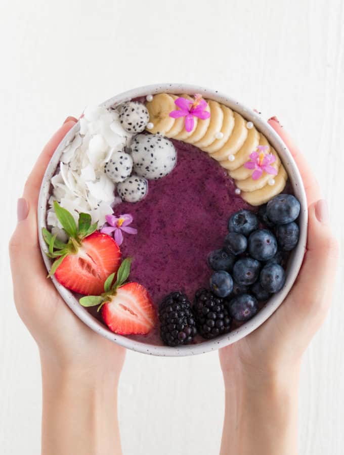 two hands holding an acai bowl