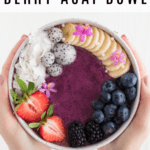two hands holding a berry acai bowl