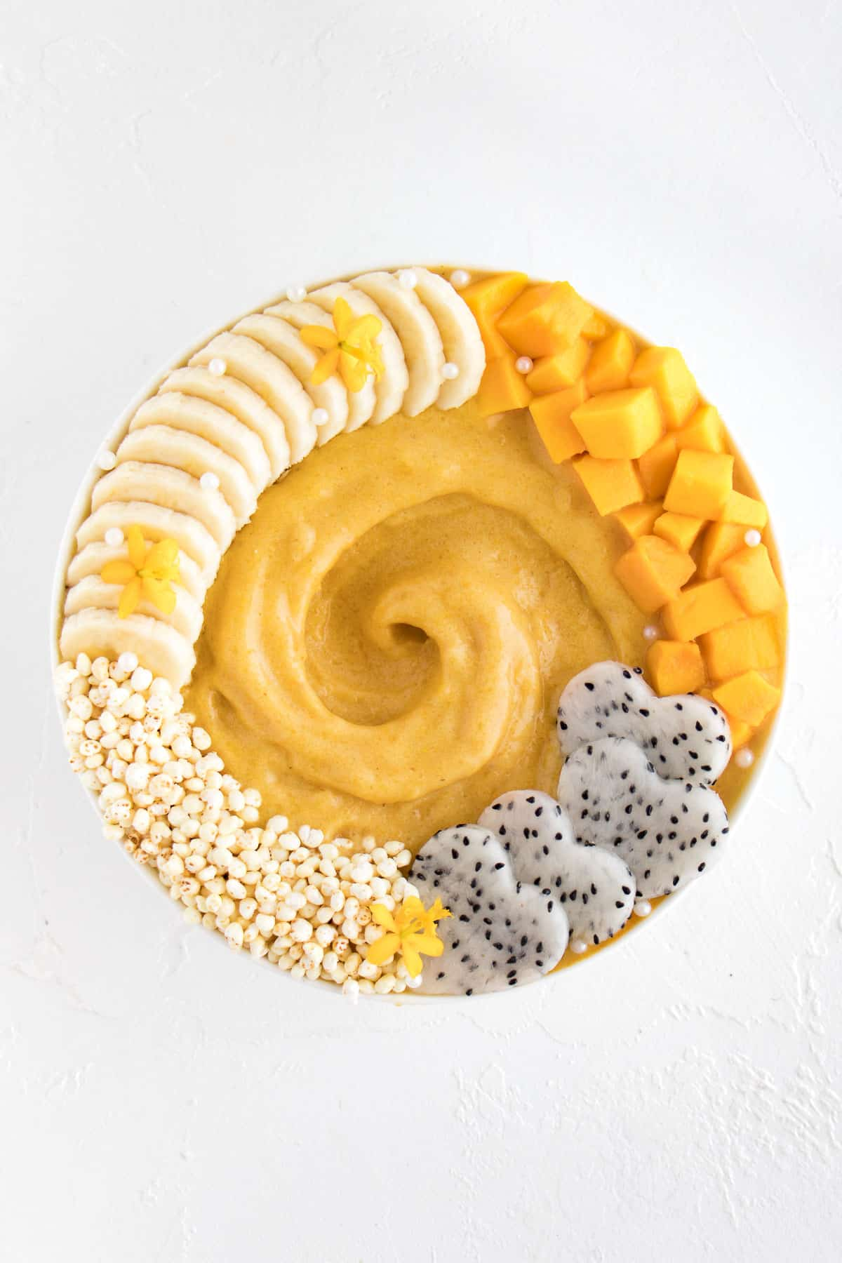 yellow smoothie in a bowl with mango, banana, and dragon fruit on top