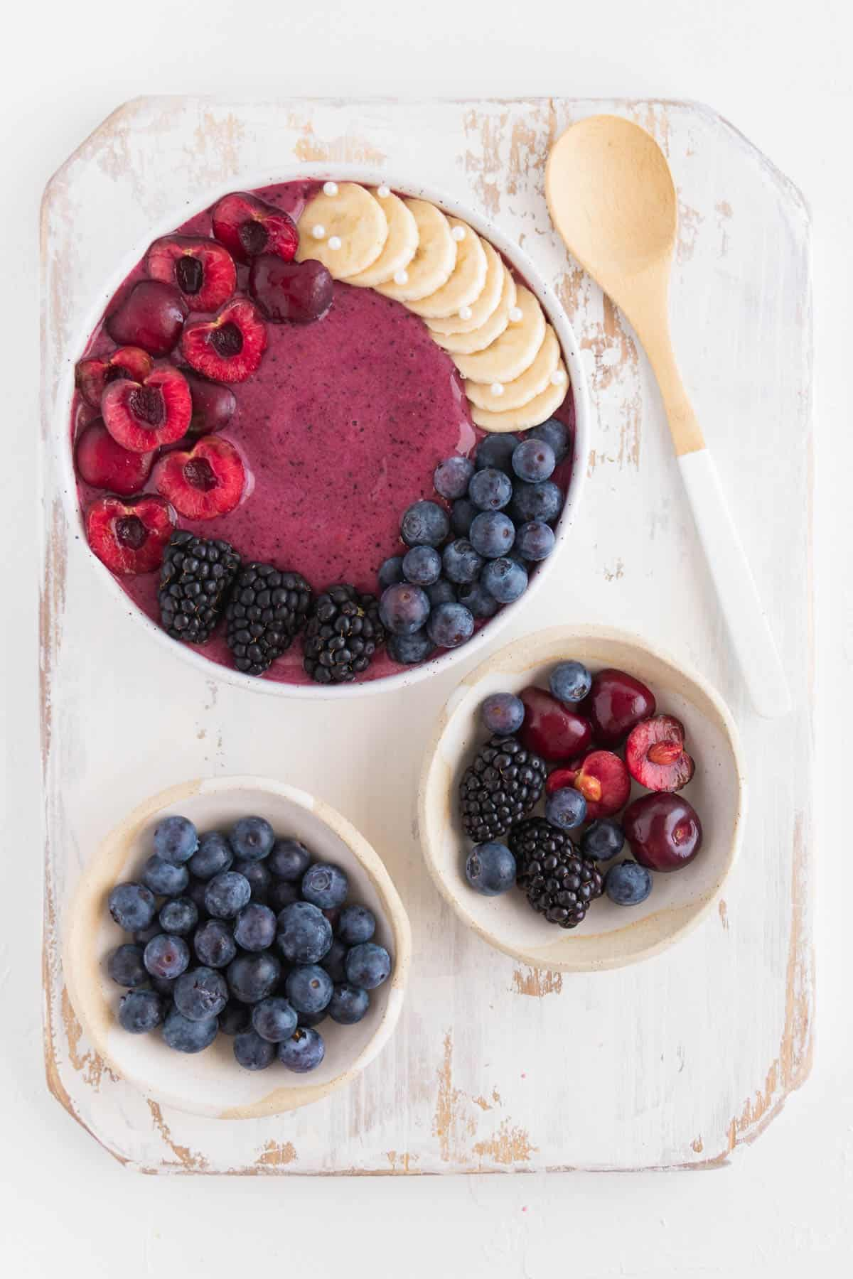 cherry smoothie bowl on top of a white distressed cutting board alongside small bowls of fruit