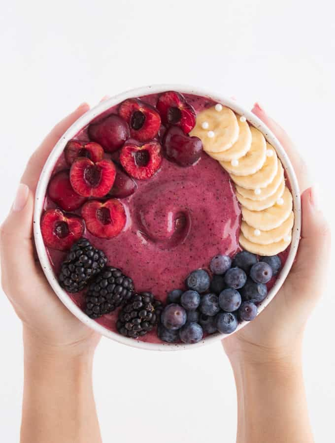 two hands holding a cherry berry smoothie bowl