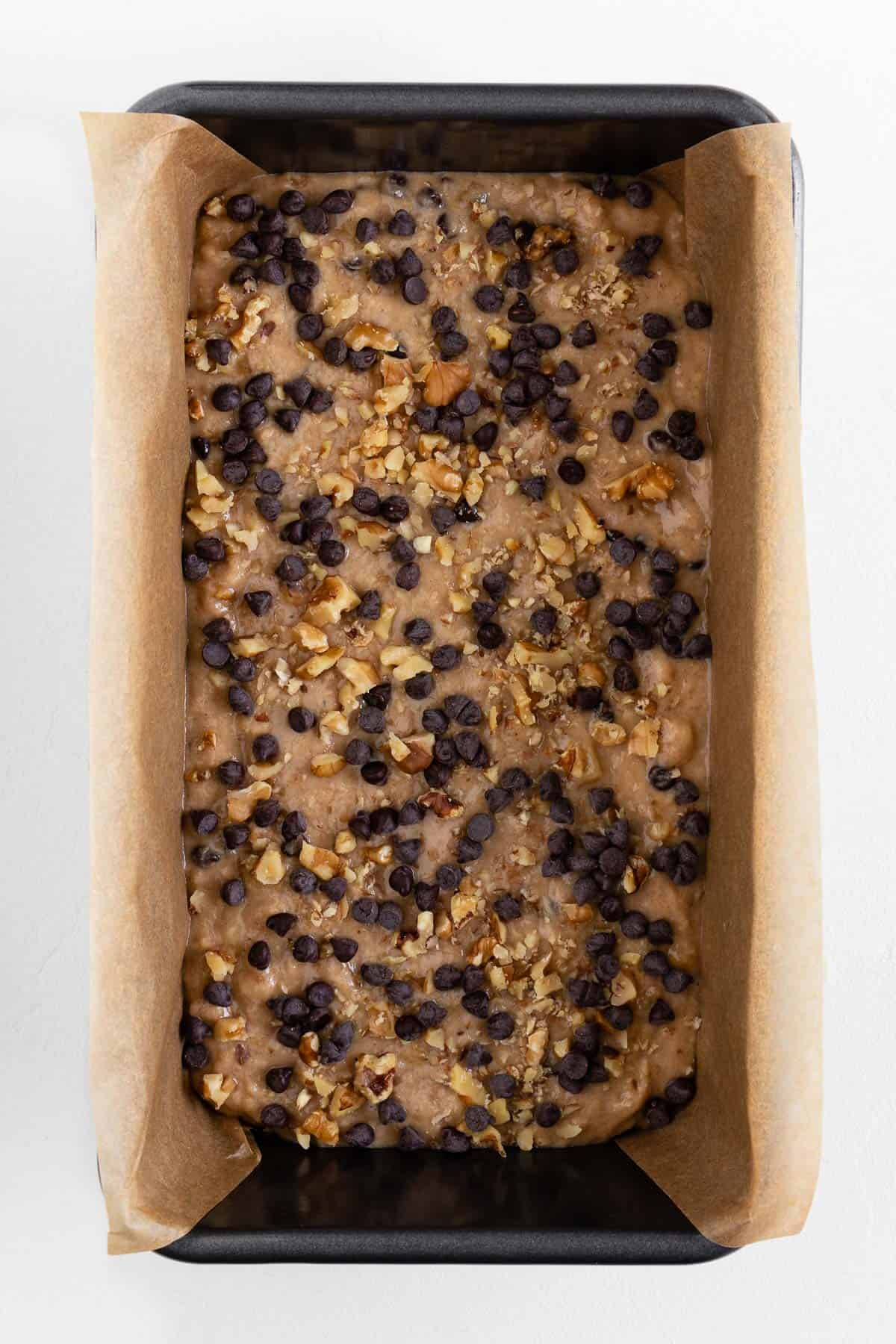 banana bread batter inside a loaf pan topped with crushed walnuts and chocolate chips