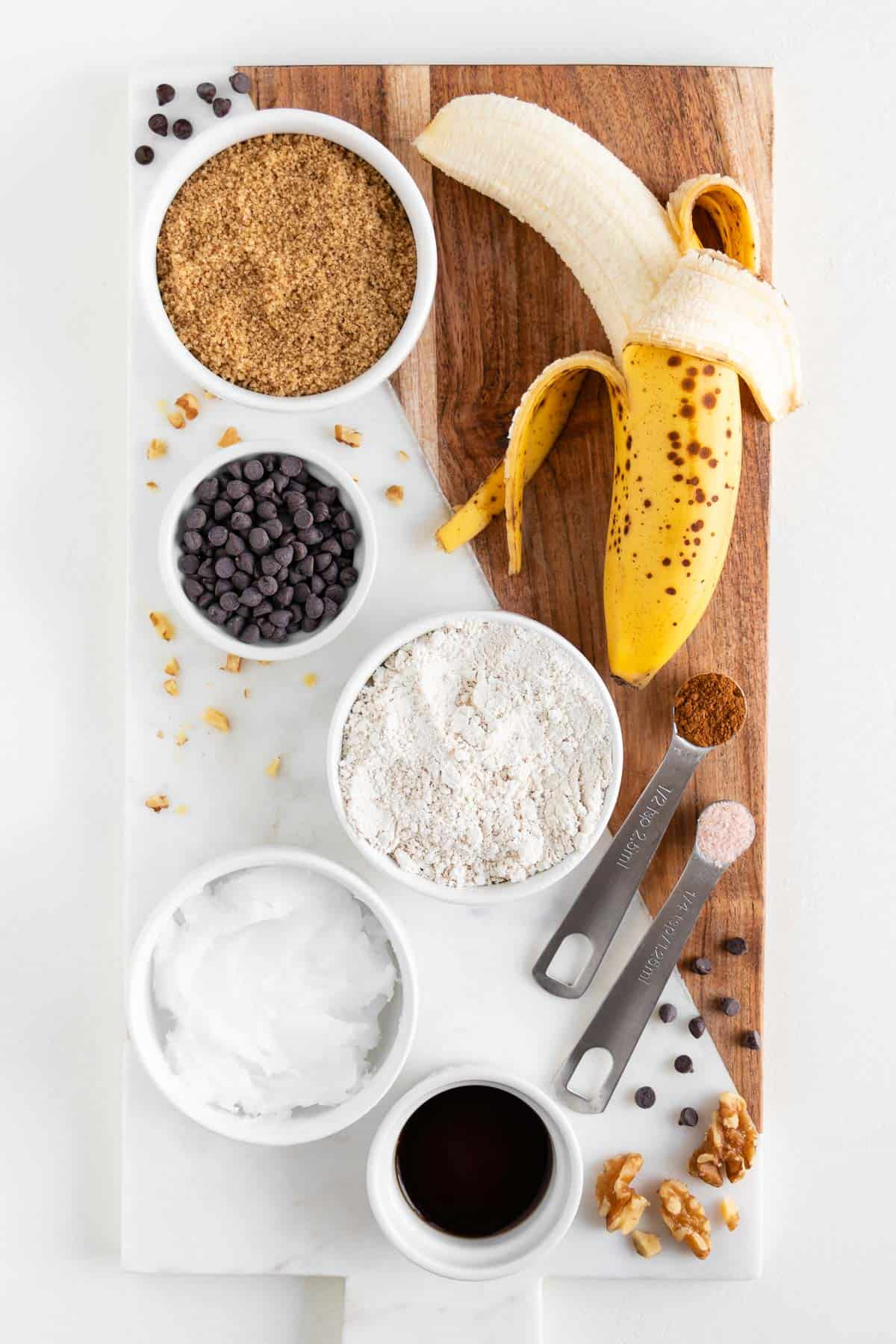 a marble and wooden board topped with bowls of brown sugar, chocolate chips, oat flour, coconut oil, vanilla extract, and a peeled banana