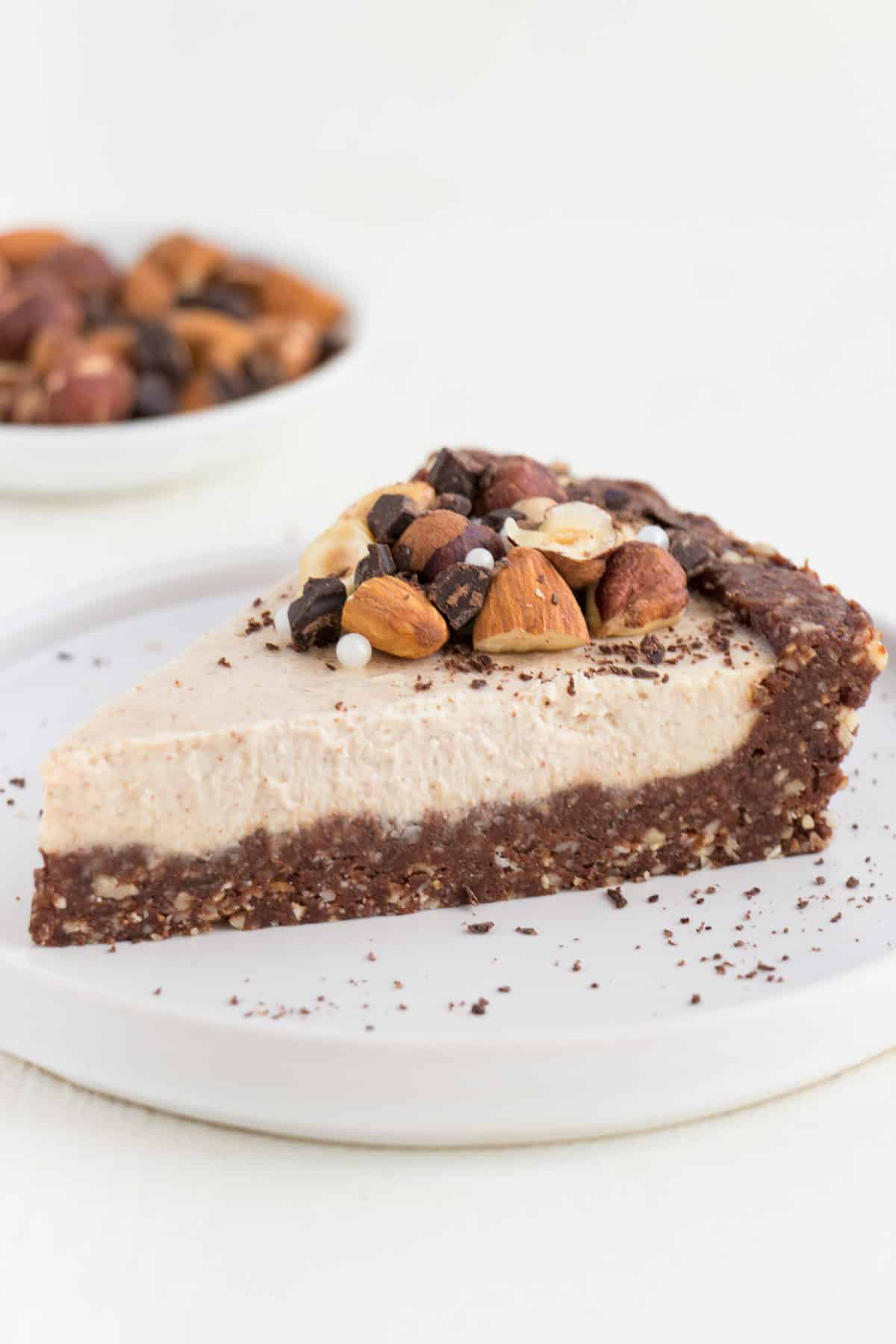 no bake chocolate almond cheesecake slice sitting on top of a small white plate