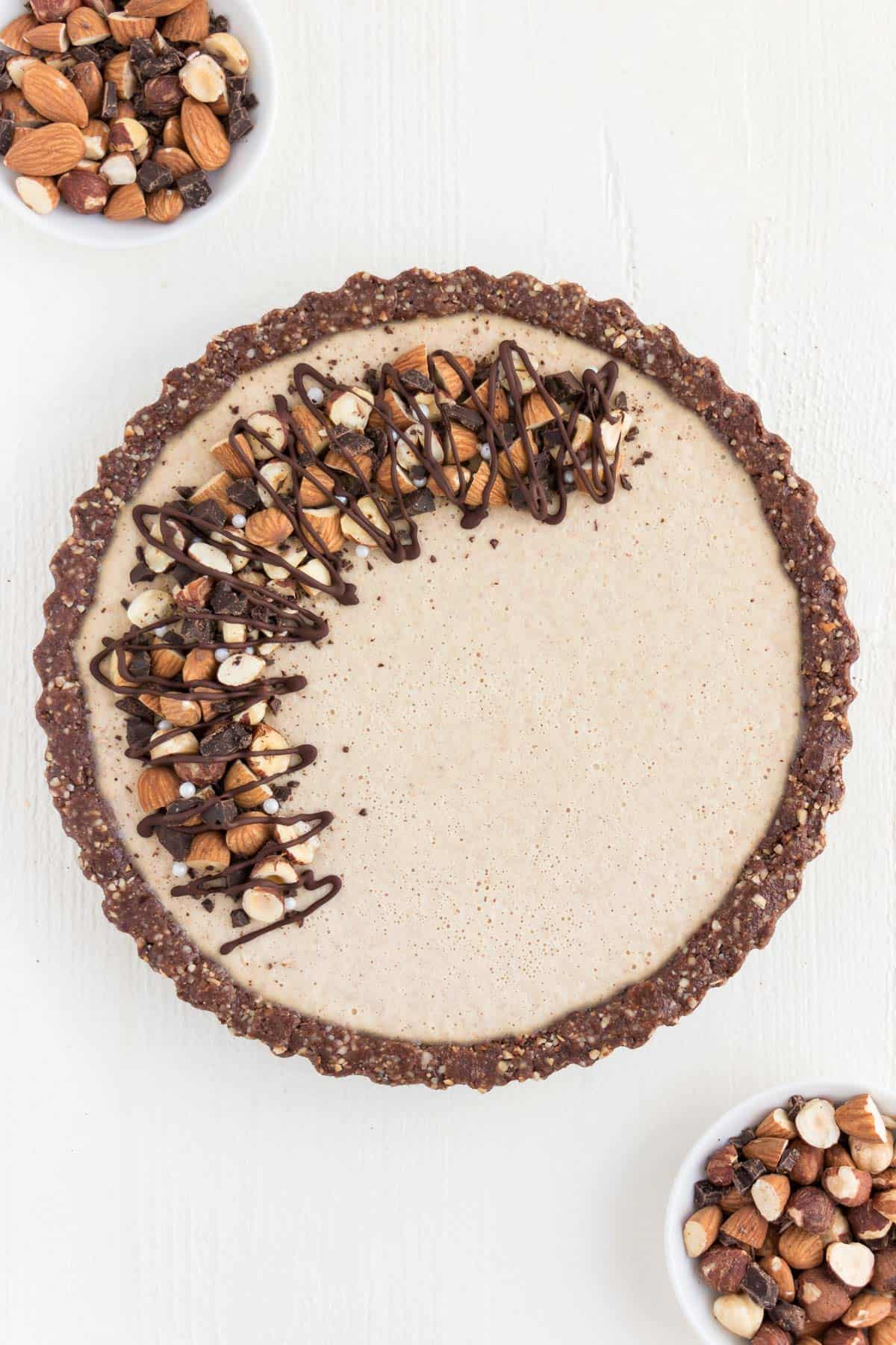 no bake chocolate almond cheesecake topped with chocolate and nuts