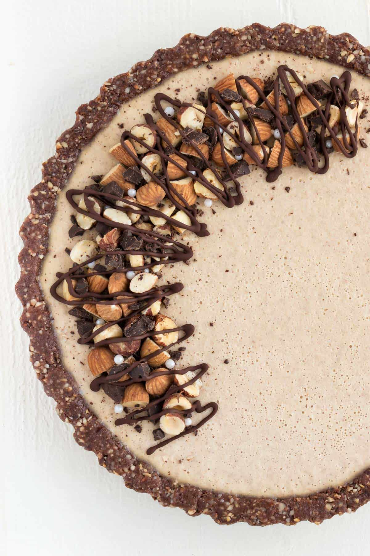 close up no bake cheesecake topped with chocolate, almonds, and hazelnuts