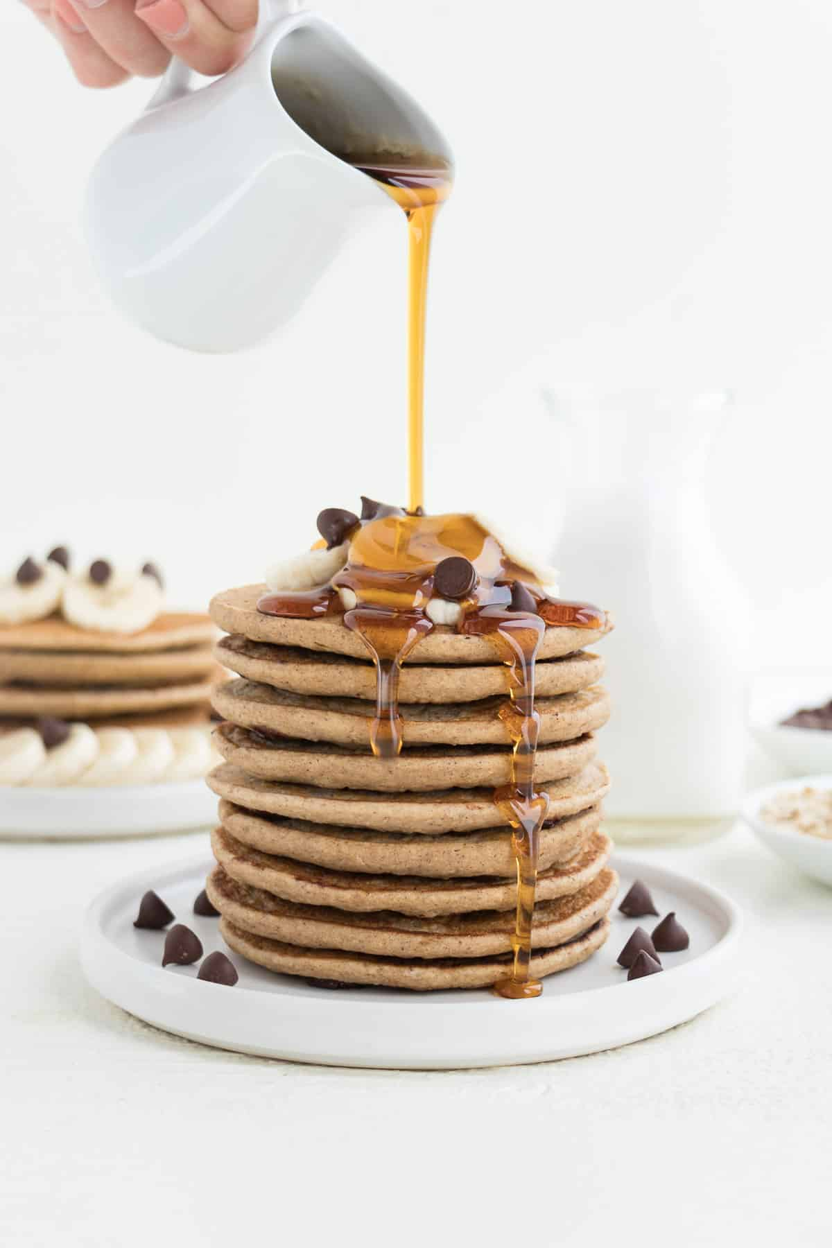 pouring maple syrup over a stack of vegan chocolate chip banana pancakes