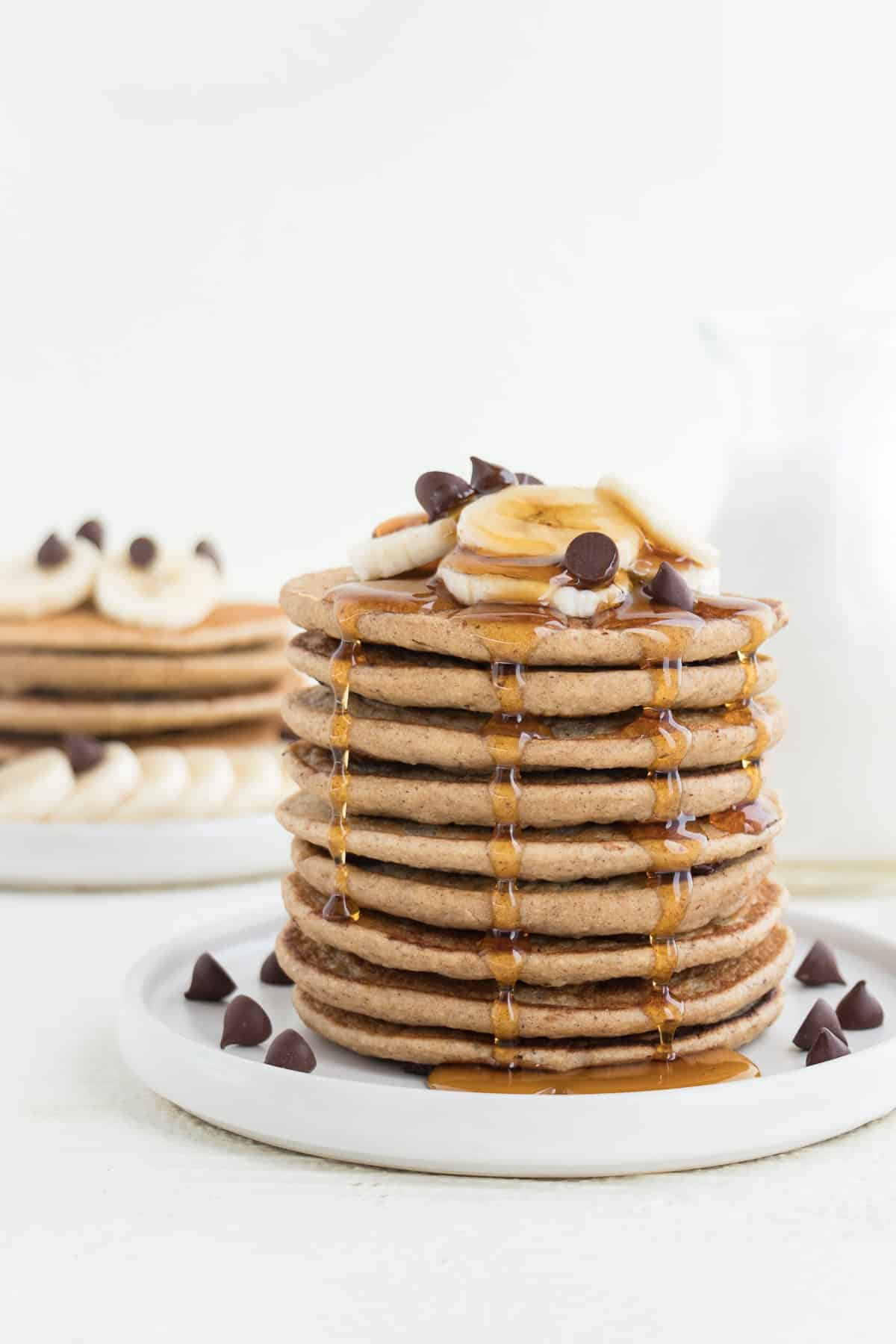 banana pancakes stacked with maple syrup, sliced banana, and chocolate chips