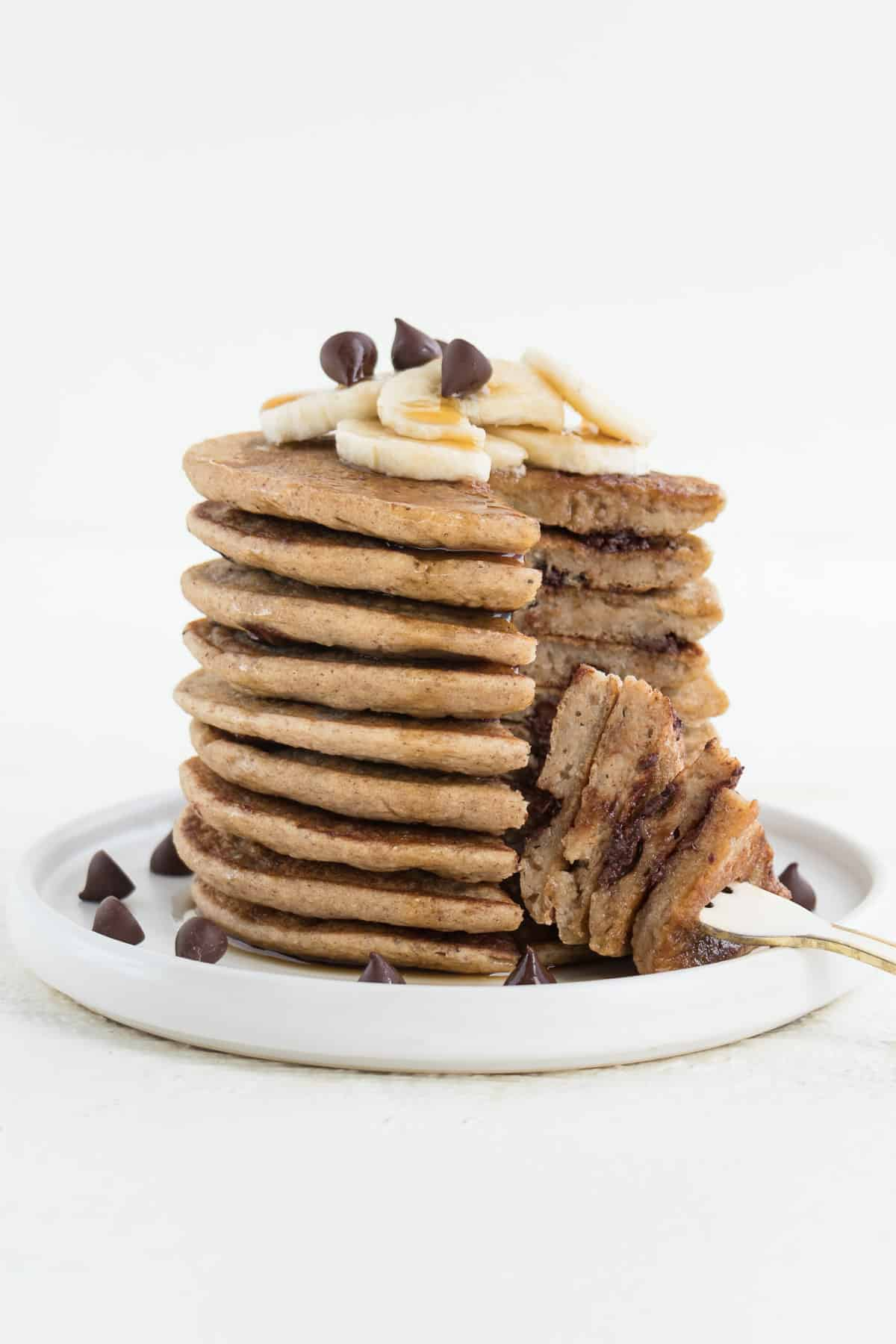 a fork cutting into a stack of vegan banana pancakes