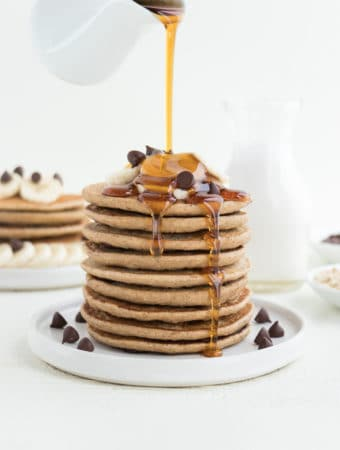 maple syrup poured over a stack of chocolate chip banana pancakes