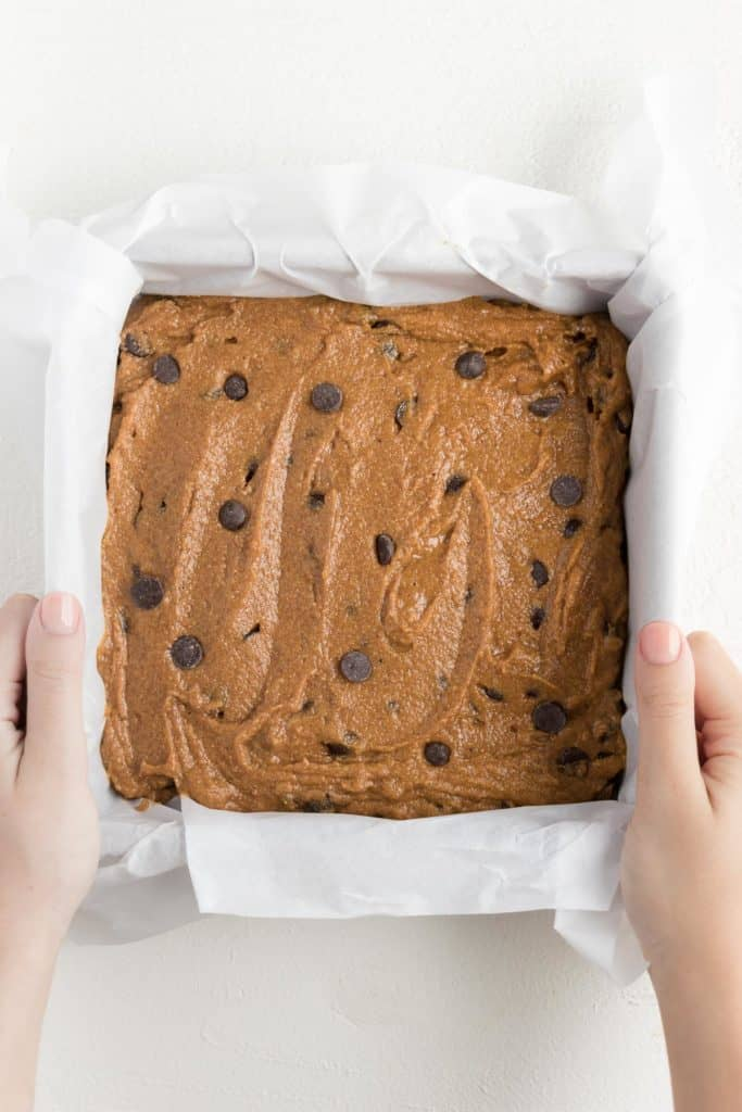 two hands holding a square pan filled with chocolate chip pumpkin bar batter