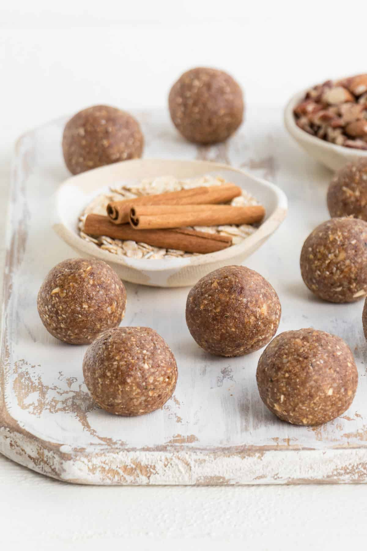 energy balls on a white distressed cutting board with cinnamon sticks