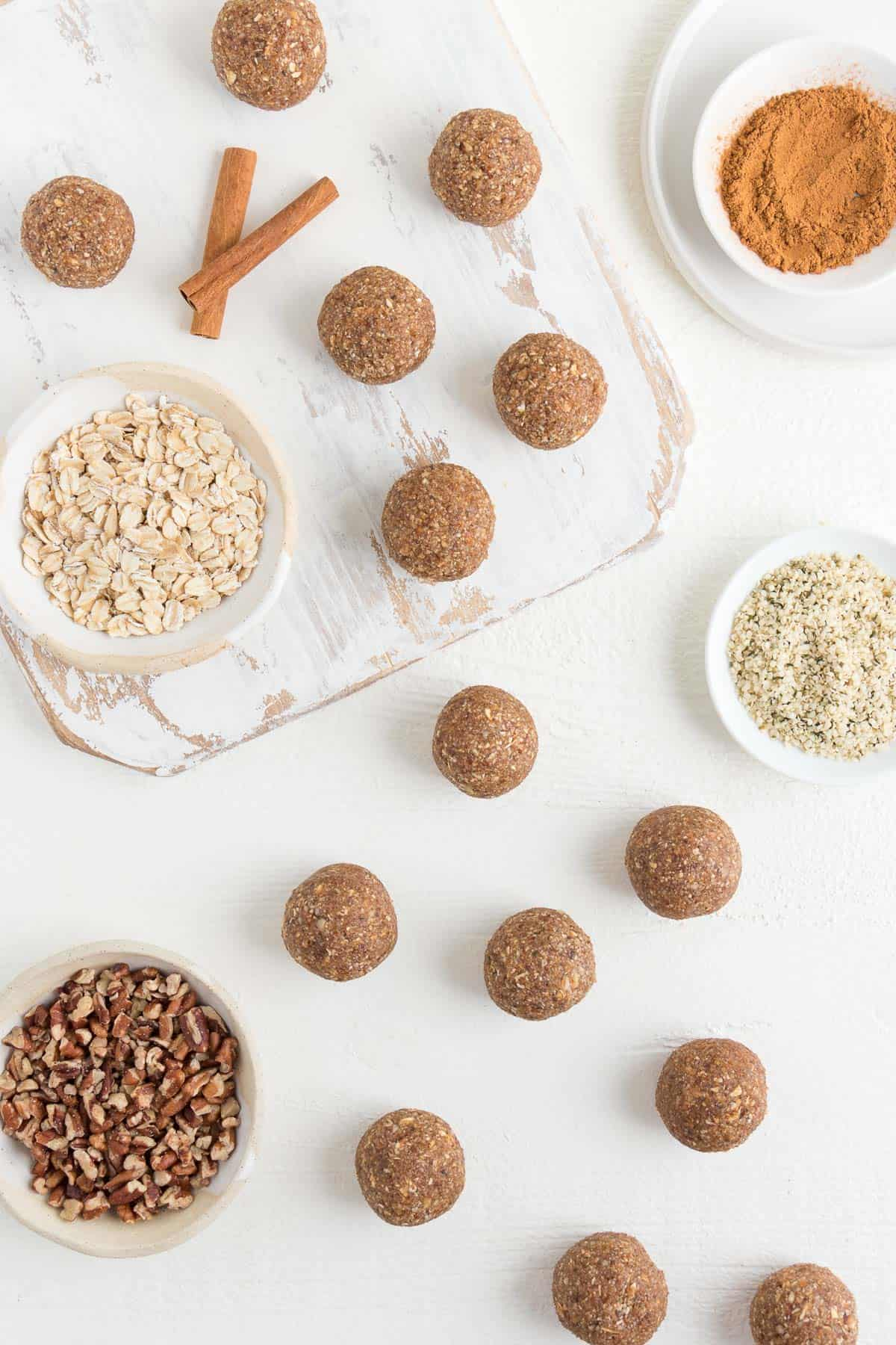 bliss balls on a white distressed cutting board alongside oats, pecans, and hemp seeds