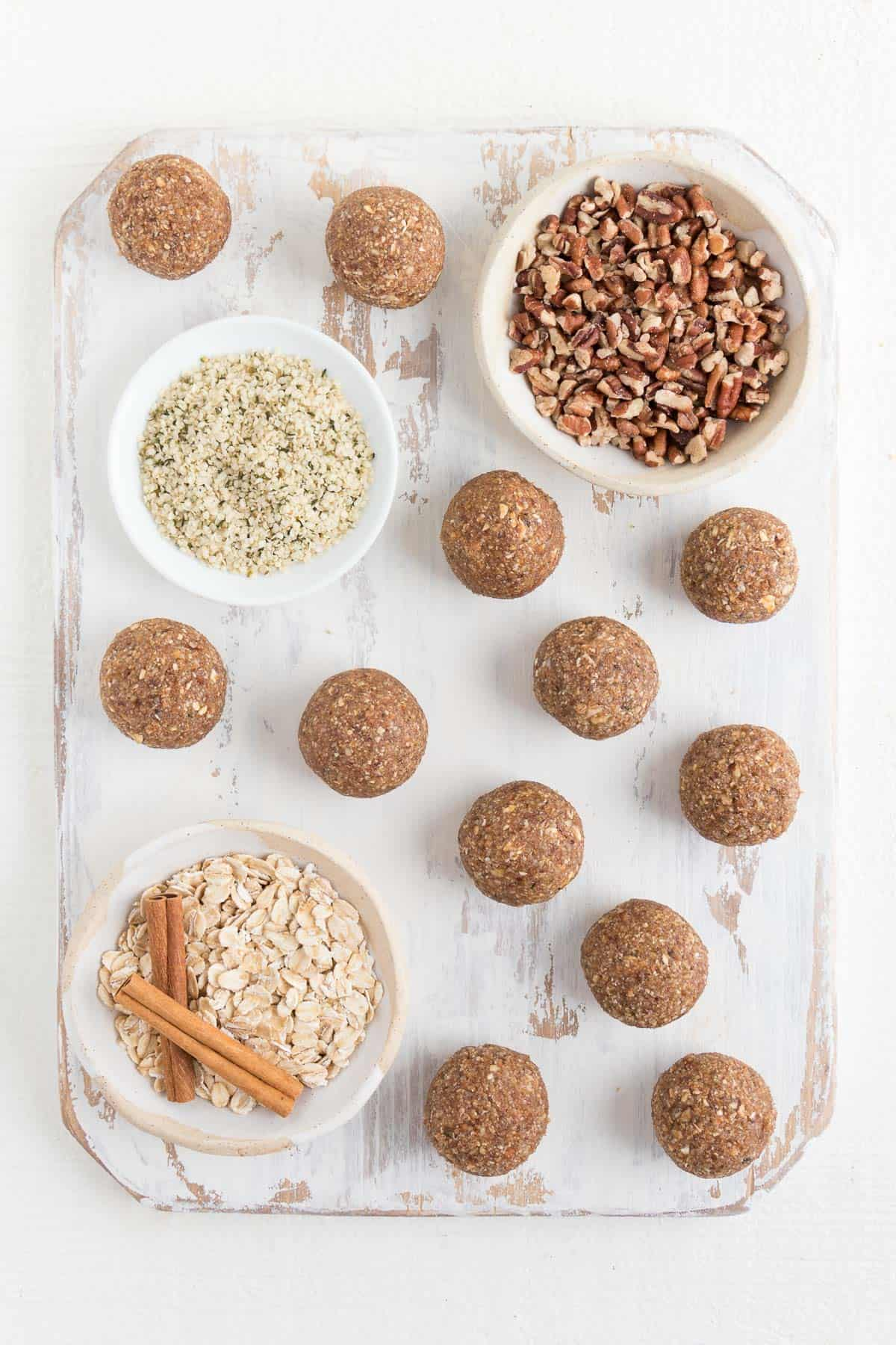 no-bake pecan balls on a white distressed cutting board with small bowls of cinnamon, oats, pecans, and hemp seeds