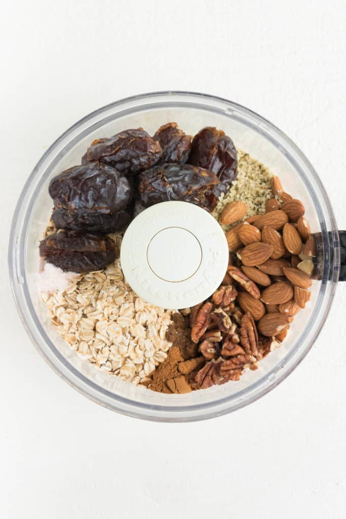 medjool dates, almonds, pecans, rolled oats, and hemp seeds inside a food processor