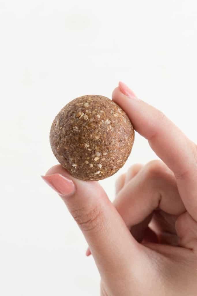 a hand holding a no-bake pecan pie bliss ball