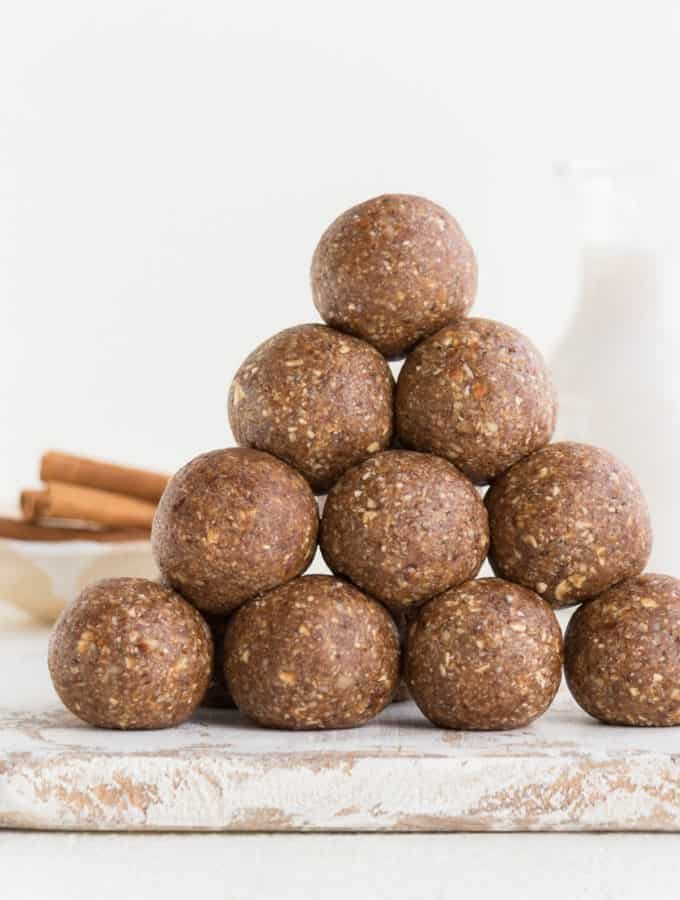 stack of pecan pie energy balls with cinnamon sticks and almond milk in the background