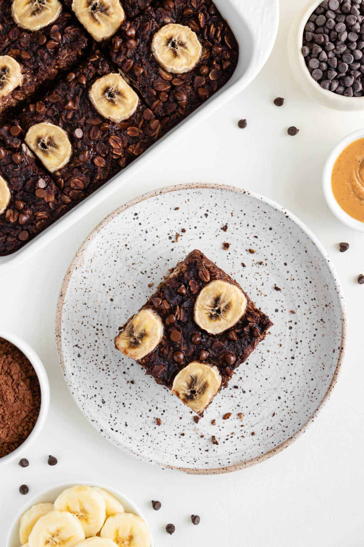a slice of chocolate baked oatmeal topped with banana and chocolate chips on a white plate surrounded by a small bowl of rolled oats and cacao powder