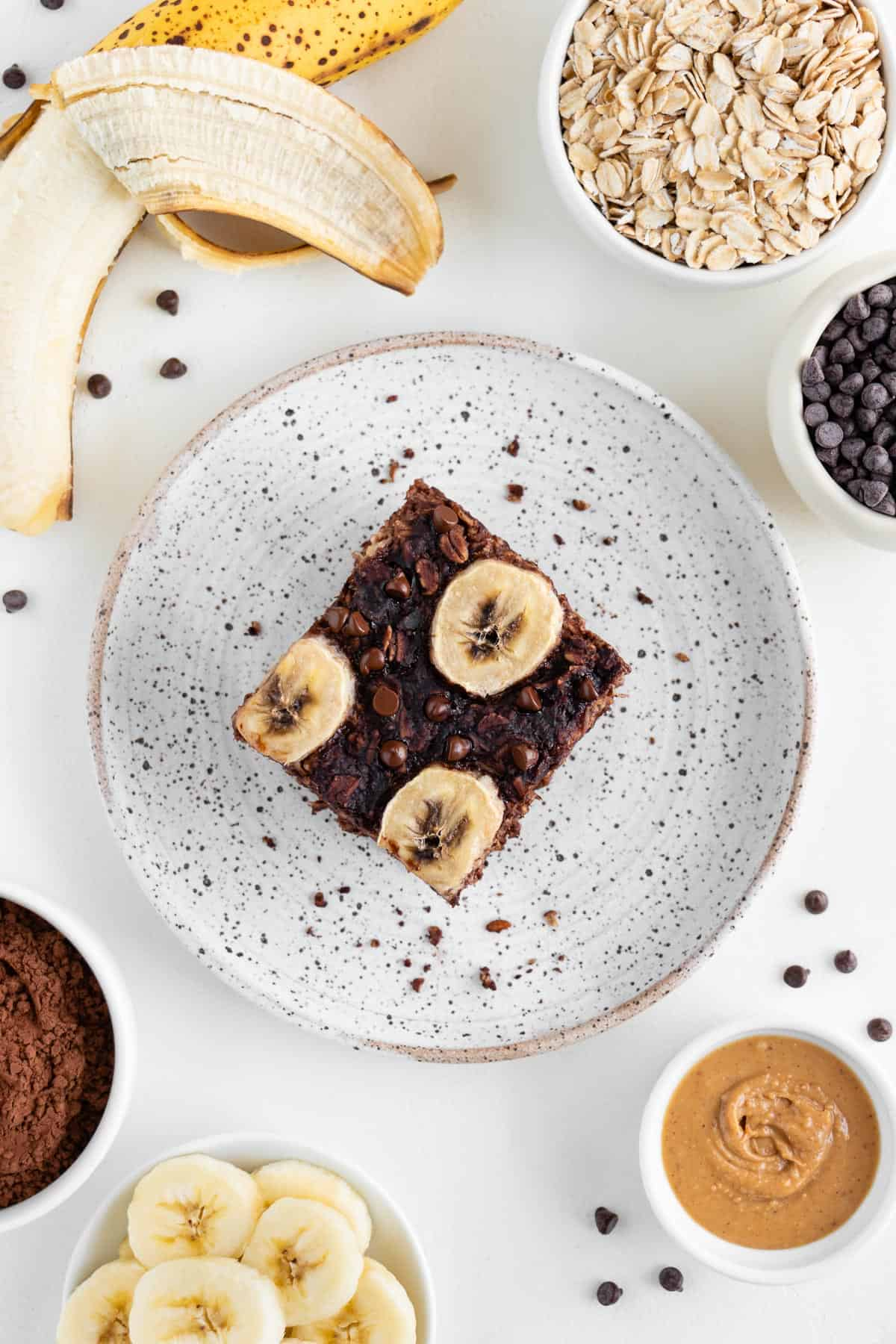 baked oatmeal with chocolate chips and bananas surrounded by rolled oats, cacao powder, and a wooden fork