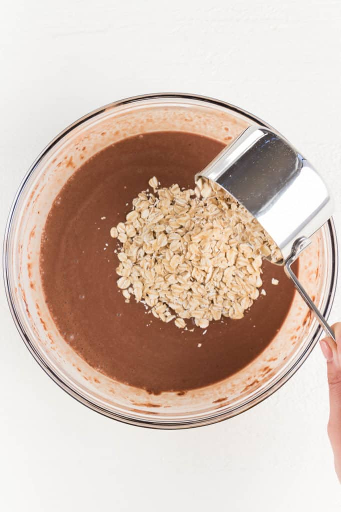 hand pouring a metal cup of rolled oats into chocolate batter inside a glass bowl