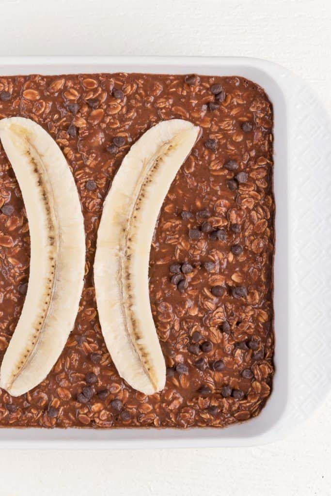chocolate banana oatmeal batter with sliced banana and chocolate chips inside a white dish