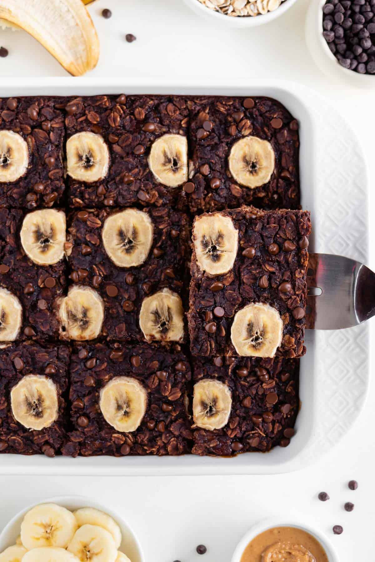 a spatula lifting a slice of vegan chocolate banana baked oatmeal out of a white baking dish