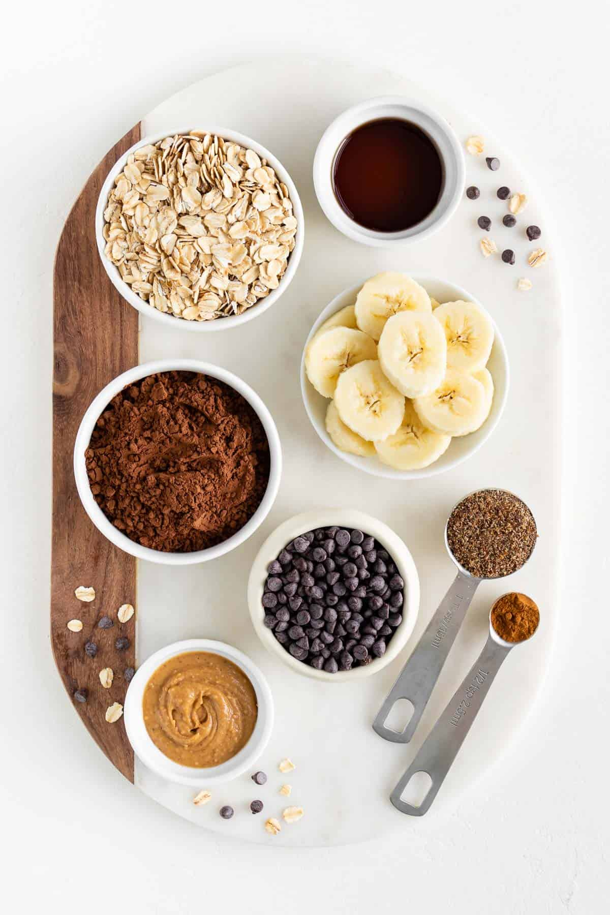 a marble board topped with small bowls containing rolled oats, cacao, bananas, peanut butter, chocolate chips, vanilla, cinnamon, and ground flaxseed