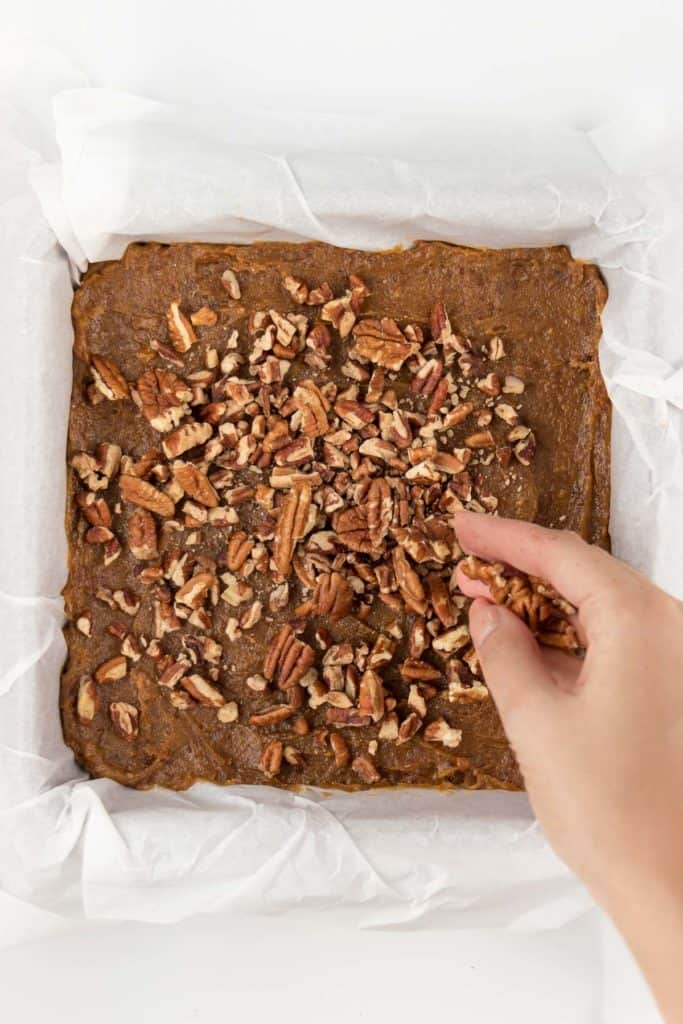 hand pouring crushed pecans on top of no-bake pecan pie bars