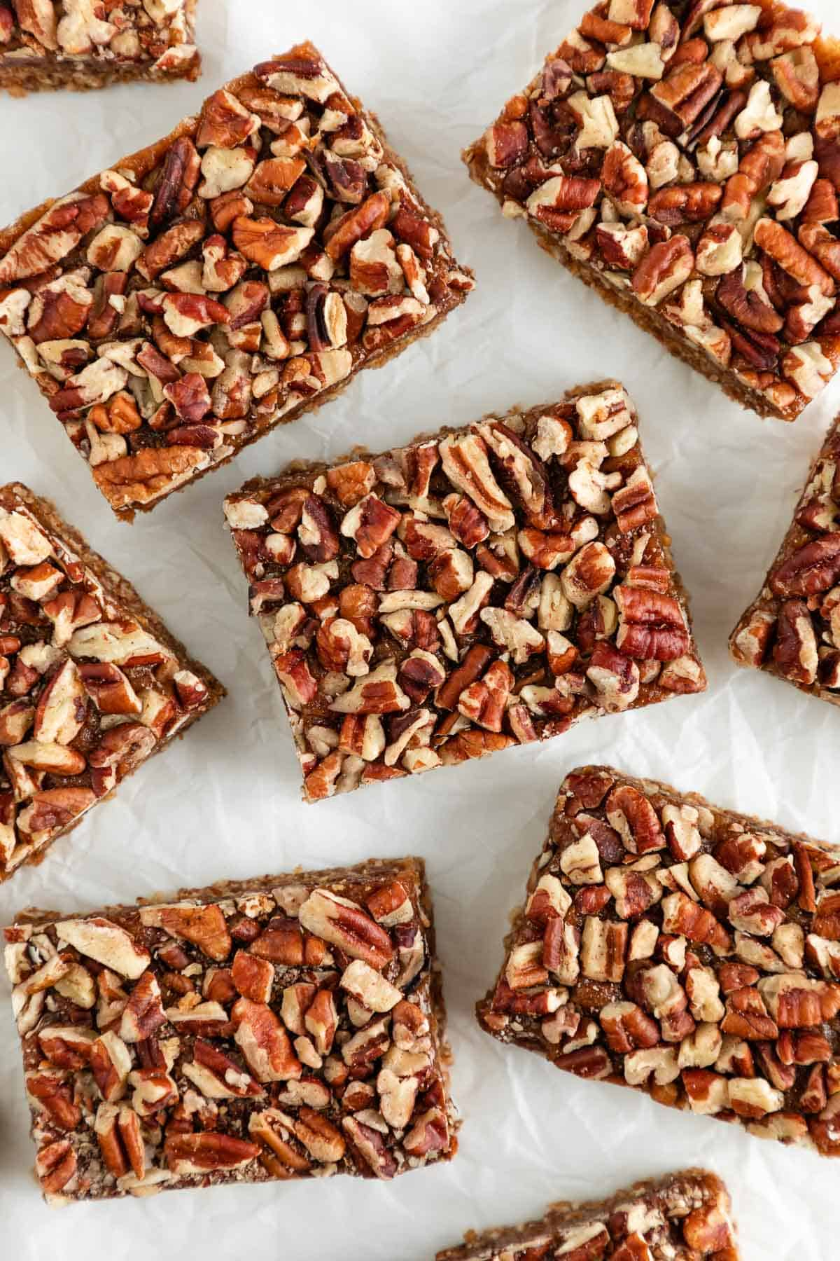 5 vegan gluten-free pecan pie bars on top of a white surface