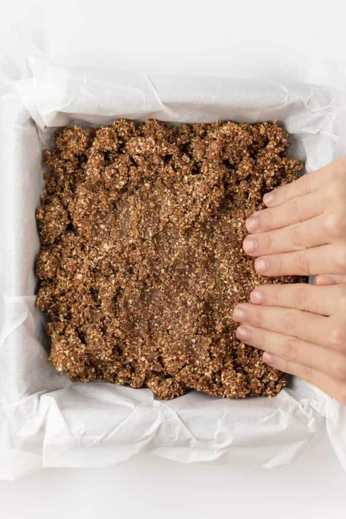 two hands pressing pie crust into a baking dish