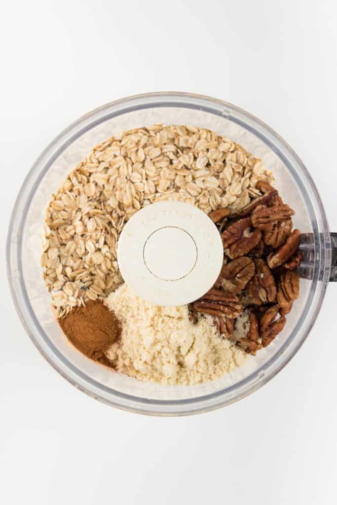 rolled oats, medjool dates, cinnamon, almond flour, and nuts inside a food processor