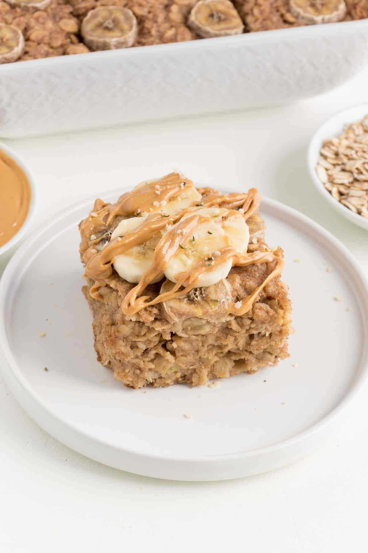 slice of peanut butter banana baked oatmeal topped with sliced bananas and peanut butter on a white plate