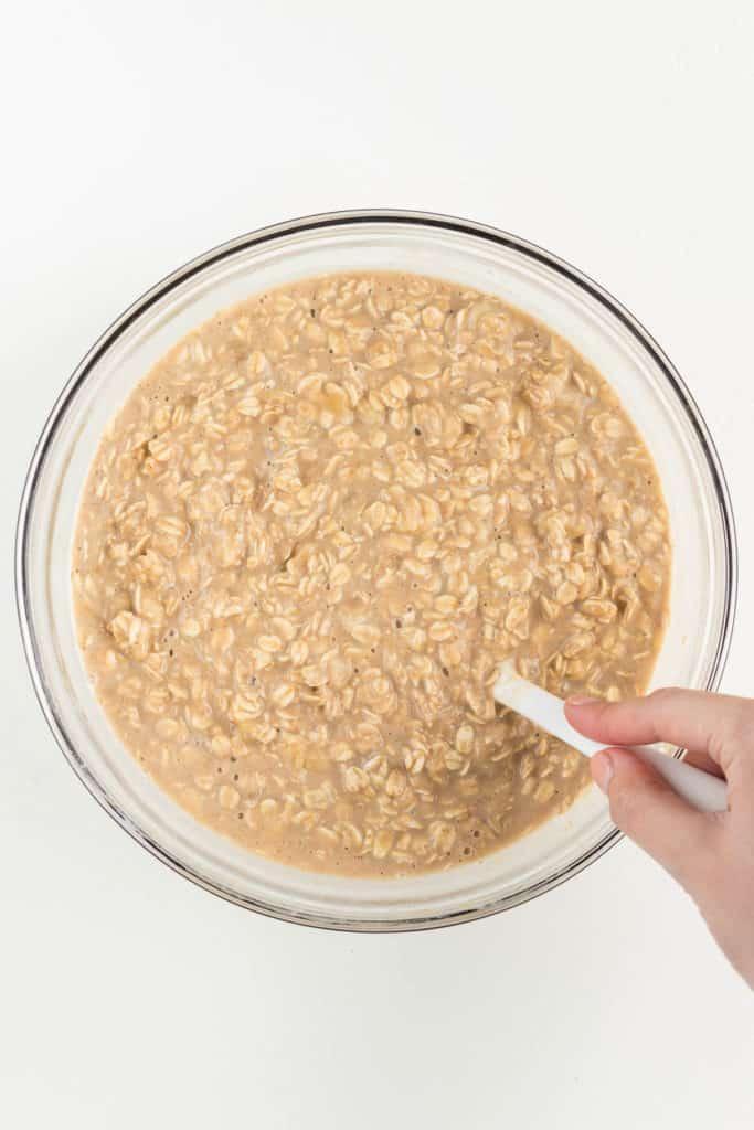 hand holding a white spatula mixing oatmeal batter